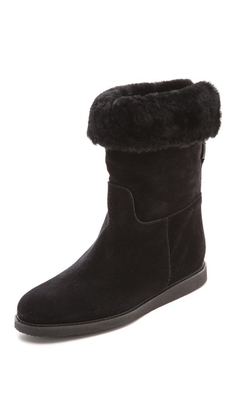 Shop Salvatore Ferragamo online and buy Salvatore Ferragamo My Ease Shearling Boots Nero - Soft shearling brings a cozy feel to these Salvatore Ferragamo boots. The folded top line reveals a peek of the napped wool lining. Tapered toe and hidden wedge heel. Rubber sole. Fur: Dyed shearling (lamb), from Spain. Leather: Calfskin. Made in Italy. Measurements Heel: 1.5in / 40mm Platform: 0.5in / 12mm Shaft: 7.5in / 19cm. Available sizes: 6,6.5,7,7.5,8,8.5,9