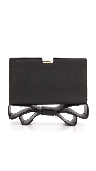 Kupi ZAC Zac Posen tasnu online i raspordaja za kupiti A ZAC Zac Posen clutch in rich saffiano leather with a signature bow at the bottom. The structured top opens with a hinged clasp. Gold tone hardware. Lined. Dust bag included. Leather: Calfskin. Weight: 11.0oz / 0.31kg. Imported, China. Measurements Height: 4.5in / 11.5cm Length: 7in / 18cm Depth: 2.5in / 6.5cm. Available sizes: One Size