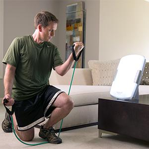 Man working out in his living room in front of the HappyLight Deluxe