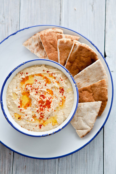 Overhead of Hummus and pita bread on white plate
