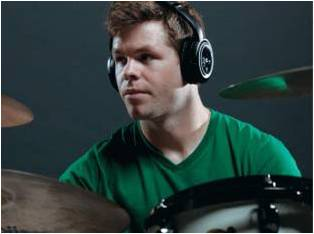 This is a picture of a man using the AWD210 headphones wile playing drums