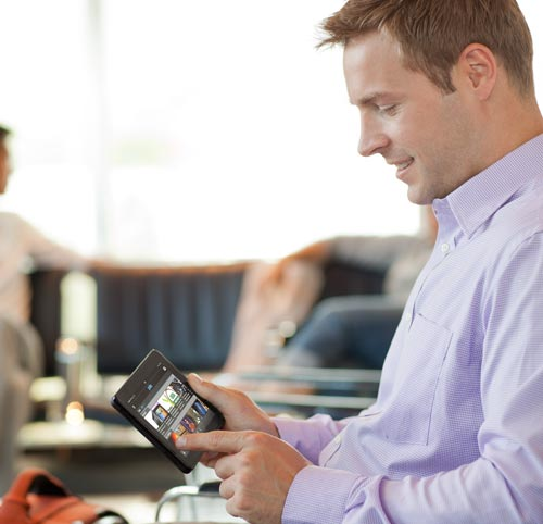 Kindle Fire: man using Kindle Fire at the airport