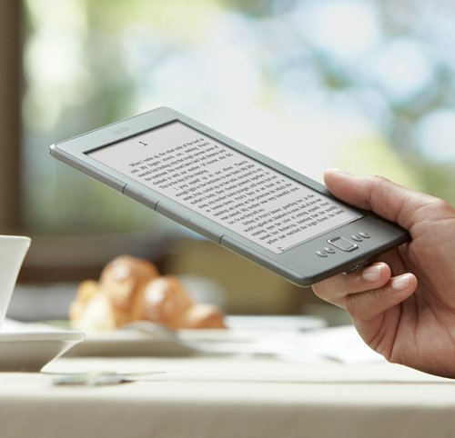 Kindle e-reader: device in hand, reading at cafe