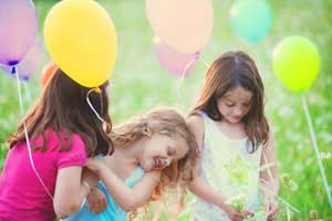 Girls with balloons in a grassy field