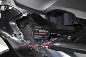 The Schumacher SE-1-12S Fully Automatic Onboard Battery Charger in use on a motorcycle battery