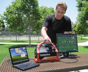 Man using the Duracell DPP-600HD Powerpack 600 to power a laptop and monitor simultaneously