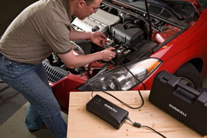 The Duracell 12 Amp Battery Charger being attached to a car battery