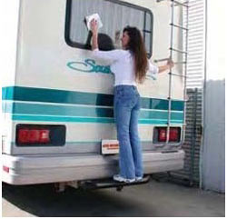 Cleaning RV rear windows using the Go Rhino! 360B 3-inch black steel hitchstep for support