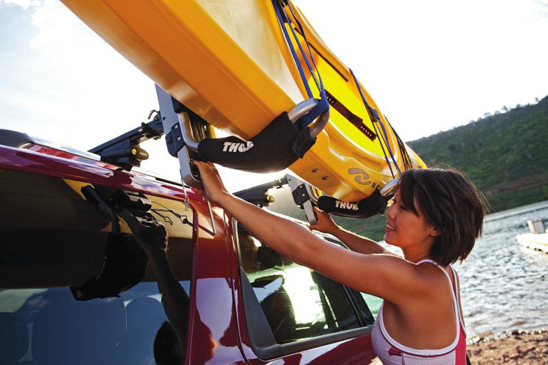 A Woman Loading A Kayak To Her Roof Rack Using The Thule