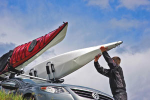 Man loading two kayaks to a vehicle using Thule 835PRO Hullaport PRO Rooftop Kayak Carriers