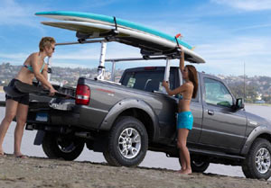 Two women loading boards onto a Thule 810 SUP Taxi Paddleboard Carrier installed on a truck