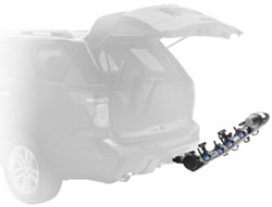 The Thule 9025 Apex four-bike hitch mount carrier in the down position with vehicle hatchback open