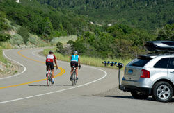 Cyclists using the Thule 9025 Apex four-bike hitch mount carrier during a ride