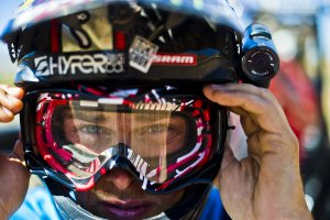 Picture shows the head of a mountain bike rider with the Contour+2 camera attached to the side of his helmet.