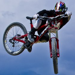 Picture shows a mountain bike and rider in mid-air against a mountain background with the rider wearing the Contour+2 camera attached to the side of his helmet.