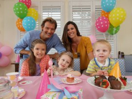 Picture shows a wide-angle view of a family seated around a table at a children's birthday party.