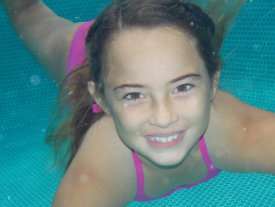 Picture shows a young girl swimming underwater in a swimming pool.