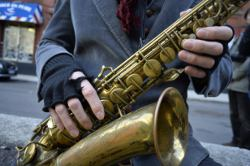 Picture shows a close-up view of a street musician's saxophone.
