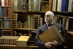 Picture shows a man standing in front of library bookshelves.