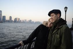 Picture shows a couple standing by the Hudson River in New York City at sunset.