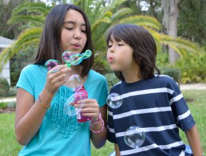 Picture shows a portrait shot of two children blowing bubbles.