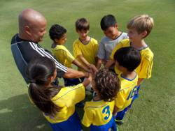 Picture shows a wide-angle view of a children's football team and their coach taken from above.