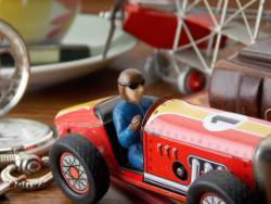Picture shows a close up view of a tin-plate model car with a model aeropland and a watch in the background.