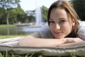 Portrait view of a woman laying on a picnic blanket on grass with a lake and fountain in the background.