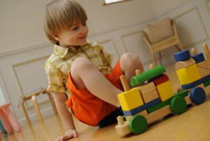 Picture of a little boy playing with a wooden train on the floor.
