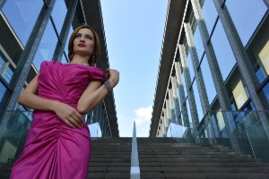 Striking, angular, ultra-wide-angle view of a woman in a bright pink dress standing on steps between two blue glass buildings.