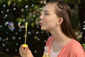 Portrait (profile head and shoulders) of a young woman blowing bubbles outdoors in natural light..