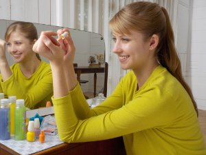 Picture shows a young woman sitting at a dressing table painting her fingernails.