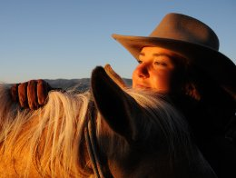 Portrait of a cowgirl resting her head on the back of her horse at sunset.