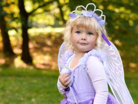 Picture shows an outdoor portrait of a young girl wearing a fairy princess costume.