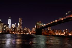 Picture shows a night cityscape of Lower Manhattan and the Brooklyn Bridge in New York City, USA.