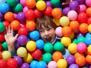Picture of a young boy buried in multi-coloured plastic balls with just his face and hand showing.