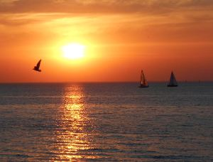 Picture shows two sailing boats and the setting sun.