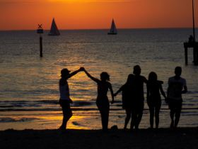 Picture shows a silhouette of people on a beach against the sunset.