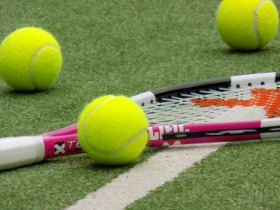Picture shows a distant telephoto view of tennis balls and a tennis racquet on a tennis court.
