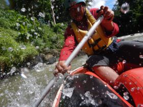 View of a canoeist from inside an inflatible boat riding the rapids.