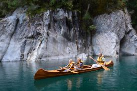 Picture shows a man and two children in a wooden canoe on clear blue water.