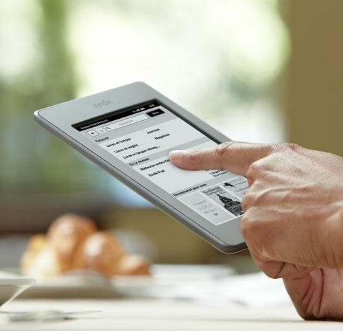 Liseuse Kindle Touch : appareil tenu en main, avec un doigt sur l'�cran tactile