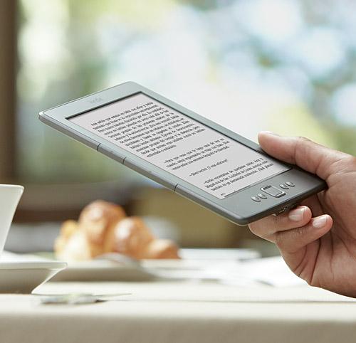 El e-reader Kindle sostenido en la mano mientras se toma un caf�