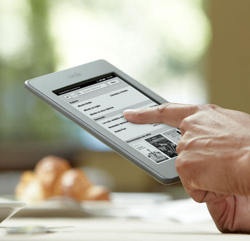 El e-reader Kindle Touch sostenido en la mano, con un dedo en la pantalla t�ctil